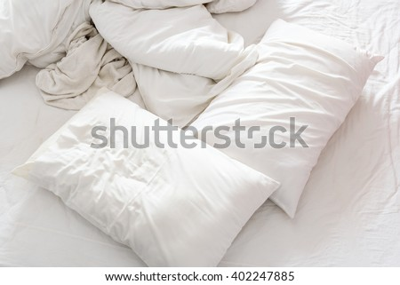 Top view of an unmade bed in a bedroom with crumpled bed sheet, a blanket, a white shower towel and two pillows after waking up in the morning. Not having bedclothes neatly arranged for sleep in. - stock photo