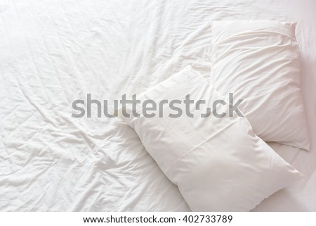 Top view of an unmade bed in a bedroom with crumpled bed sheet and two pillows after waking up in the morning. An accommodation that is not having bedclothes neatly arranged for guests to sleep in. - stock photo