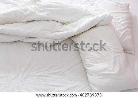 Top view of an unmade bed in a hotel bedroom with crumpled bed sheet, a white blanket / duvet and two pillows after waking up in the morning. Not having bedclothes neatly arranged for sleep in. - stock photo