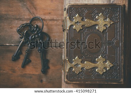 top view of antique book cover, with brass clasps and old keys. vintage filtered and toned. selective focus  - stock photo