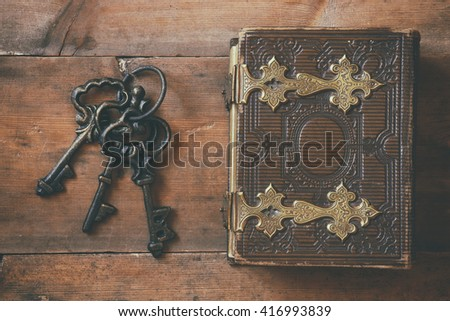 top view of antique book cover, with brass clasps and old keys. vintage filtered and toned  - stock photo