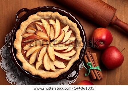 Top view of apple pie, cinnamon sticks and apples - stock photo