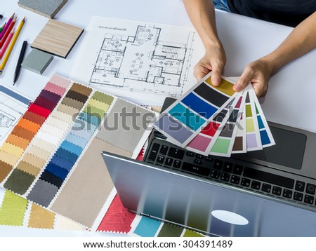 Top view of architects hands working with laptop computer, material sample on desk - stock photo