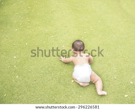 Top view of Asian baby boy crawling on the green grass field at the outdoor park. Back side of baby crawling.  - stock photo