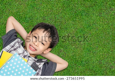 Top view of Asian boy smiles and lying on grass field - stock photo