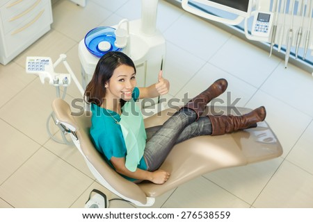 Top view of asian woman looking towards the camera in a dental studio - stock photo