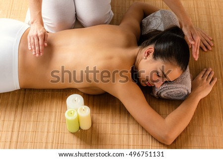 Top view of attractive woman at alternative treatment session. Reiki therapist working on energy channels on female spine.