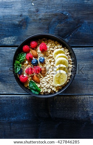 Top view of balanced breakfast composition with oat flakes, fresh berries, nuts and banana in black bowl on rustic wooden background, border. Healthy lifestyle and diet food concept. Flat lay.  - stock photo