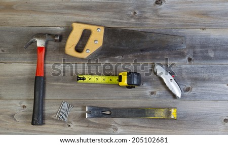 Top view of basic home repair tools consisting of wood saw, hammer, nails, box cutter, pry bar and tape measure on rustic wooden boards - stock photo