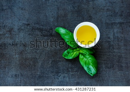 Top view of basil leaves and olive oil on black slate, food background with copy space. Simple food concept. - stock photo