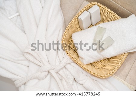 Top view of bathing robe with spa and wellness objects in basket. - stock photo