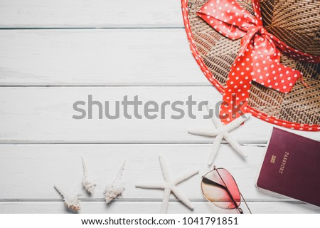 Top view of beach summer accessories with copy space. Lay flat holiday fashion background on white wooden table or floor. Horizontal frame for travel concept.