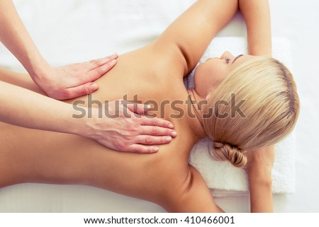 Top view of beautiful blonde girl lying on front of her body while a massage therapist is massaging her back - stock photo