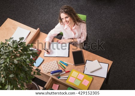 Top view of beautiful business woman in white business suit working in office. Happy and cheerful lady looking in front of her. - stock photo