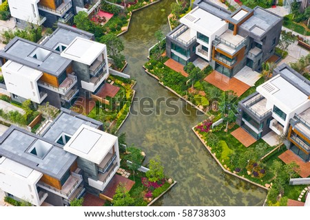 Top view of beautiful villa houses besides water. - stock photo