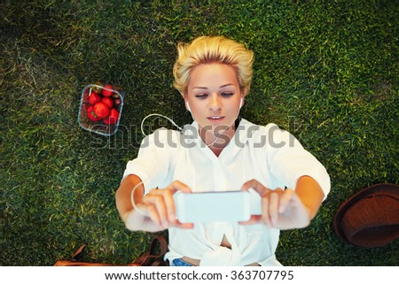 Top view of beautiful woman enjoying music in headphones and photographing herself on mobile phone camera, charming blonde hair female taking picture with cell telephone during rest in a meadow - stock photo