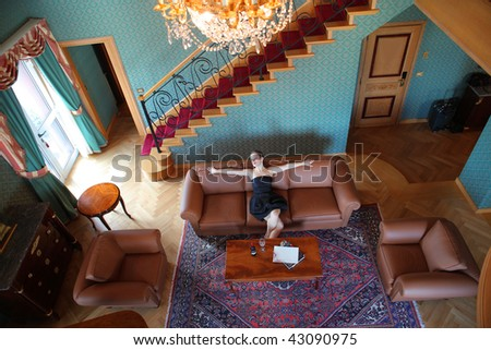 top view of beautiful woman seated on the sofa of luxury living room - stock photo