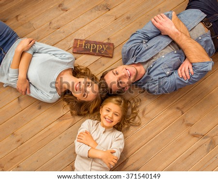 Top view of beautiful young family looking in camera and smiling while lying on wooden floor at home - stock photo