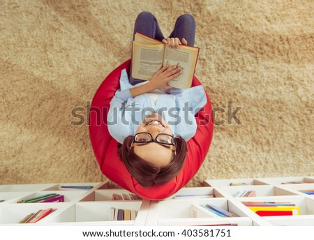 Top view of beautiful young girl in eyeglasses reading a book, looking at camera and smiling while sitting at home - stock photo