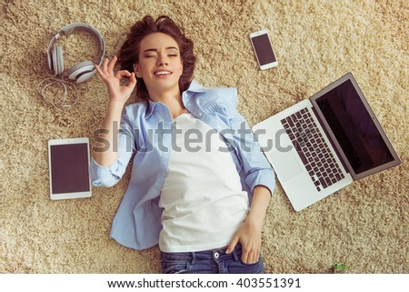 Top view of beautiful young girl showing Ok sign, looking at camera and smiling, lying among gadgets on carpet at home