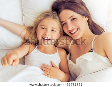 Top view of beautiful young mother and her daughter hugging, looking at camera and smiling while lying in bed at home - stock photo