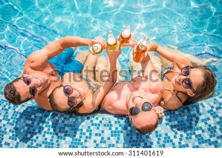 Top view of beautiful young people having fun in swimming pool, smiling and drinking beer. - stock photo
