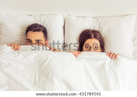 Top view of beautiful young woman and her man hiding behind blanket and looking at camera while lying in bed at home - stock photo