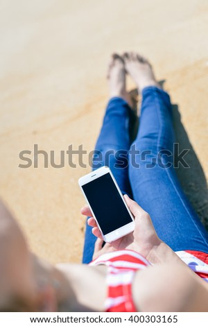 Top view of beautiful young woman using smart phone on beach sandy background. communication technology concept - stock photo