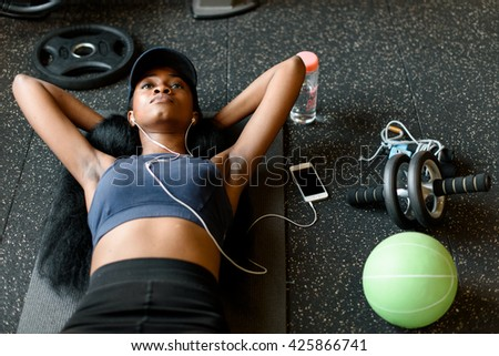 Top view of black sexy fitness instructor woman doing press ups at the gym and listening to music in earphones - stock photo