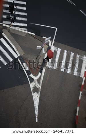 Top view of black & White cross road: Traffic island, pedestrian crossings and traffic lights on a rainy day. A Pedestrian with a red umbrella cross the street. - stock photo