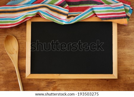 top view of blackboard and wooden spoon over wooden table - stock photo