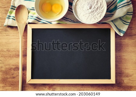 top view of blackboard and wooden spoon over wooden table. filtered image  - stock photo
