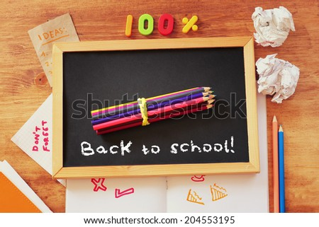 top view of blackboard with the phrase back to school, stack of pencils and crumpled paper. - stock photo