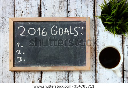 top view of blackboard with the phrase 2016 goals over wooden board with coffee  - stock photo