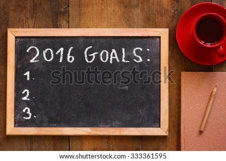 top view of blackboard with the phrase 2016 goals over wooden board with coffee and notebook - stock photo