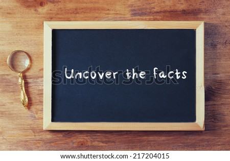 top view of blackboard with the phrase uncover the facts and magnifying glass over wooden board. - stock photo