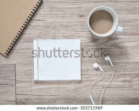 Top view of blank compact disc (CD) with cover, earphones, notebook and coffee on wooden background ( Space for picture and text ) - stock photo