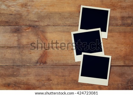 top view of blank instant photos album on wooden background. vintage filtered image. ready to put images  - stock photo