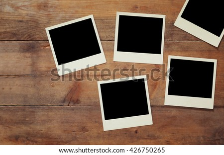 top view of blank instant photos album on wooden blue background. vintage filtered image. ready to put images  - stock photo
