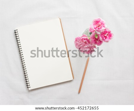 Top view of blank notebook and flower on white workspace background. Focus flower. - stock photo