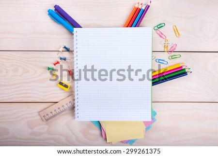 Top view of blank notebook and school supplies on the  wood background - stock photo