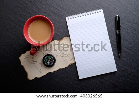 Top view of blank notebook, pen, piece of world map, compass and milk tea, flat lay. Background for anything. - stock photo