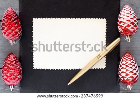 Top view of  blank paper and pen with red christmas decoration on a black board. - stock photo
