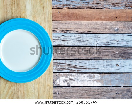 Top view of blank plate on table top with rustic wooden copy space background