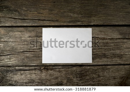 Top view of blank white peace of paper ready for your message, text or product on textured wooden background. - stock photo