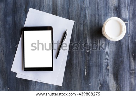 Top view of blank white tablet, paper sheets, pen and take away coffee cup on dark wooden desktop. Mock up