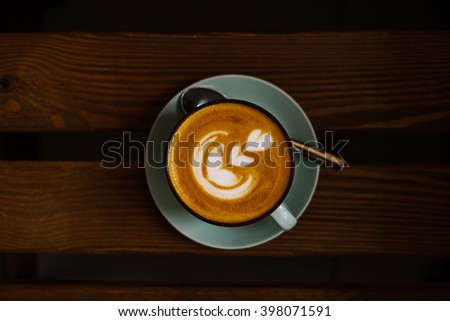 Top view of blue cup of espresso coffee with saucer on wooden rustic table. - stock photo