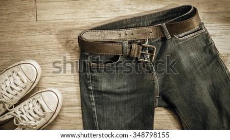 Top view of blue jeans with leather belt and dirty white sneaker shoes  on the wooden background  - stock photo