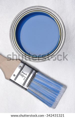 Top view of blue paint can with brush on grey metal background