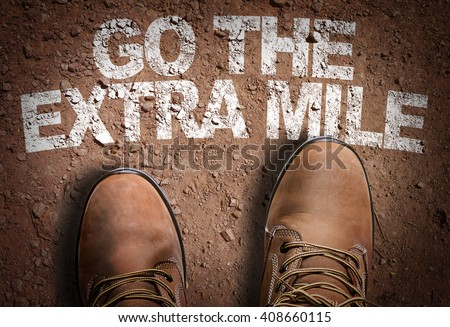 Top View of Boot on the trail with the text: Go The Extra Mile - stock photo